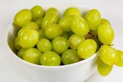 Uva senza semi verde in una ciotola bianca profonda su un racconto bianco che aspetta per essere mangiato fotografia stock