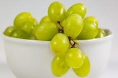 Uva senza semi verde in una ciotola bianca profonda su un racconto bianco che aspetta per essere mangiato immagine stock