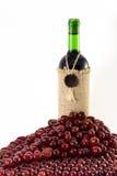 Uvas alrededor de la botella de vino Foto de archivo libre de regalías