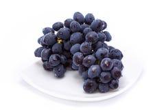 Uvas azuis em uma placa branca fotos de stock