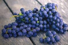 Uvas azules y púrpuras maduras en la tabla de madera gris vieja imagen de archivo