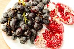 Uvas azules y semillas rojas de la granada Foto de archivo libre de regalías