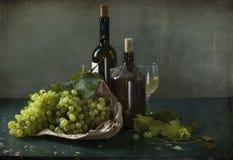 Uvas blancas, botellas de vino y un vidrio de vino Foto de archivo libre de regalías