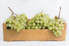 Uvas blancas frescas en una caja de madera en un fondo blanco Foto de archivo libre de regalías