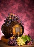 Uvas blancas y rojas con el barril de vino Foto de archivo libre de regalías