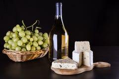 Uvas, botella de vino y queso verde en fondo negro Fotos de archivo libres de regalías