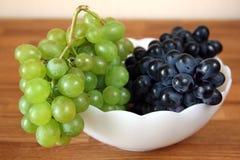 Uvas brancas e vermelhas frescas na bacia branca Fotografia de Stock Royalty Free