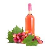 Uvas com o frasco da folha e de vinho isolado no branco foto de stock