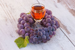 Uvas con la hoja y el vidrio de vino en la tabla de madera en jardín Fotos de archivo