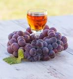 Uvas con la hoja y el vidrio de vino en la tabla de madera en jardín Imagen de archivo
