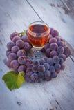 Uvas con la hoja y el vidrio de vino en la tabla de madera en jardín Fotografía de archivo