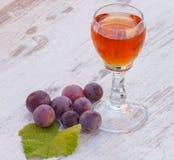 Uvas con la hoja y el vidrio de vino en la tabla de madera en jardín Fotos de archivo libres de regalías
