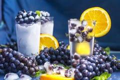 Uvas congeladas no vidro da água com close-up da laranja e do gelo Fotografia de Stock Royalty Free