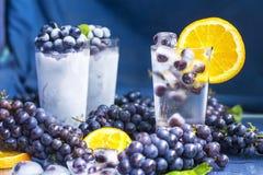 Uvas congeladas no vidro da água com close-up do gelo Imagens de Stock Royalty Free