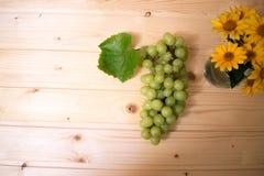 Uvas de uvas en una tabla de madera Imagen de archivo libre de regalías
