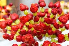 Uvas de la fresa en un palillo Dé fruto en un palillo en una tabla de banquete Foto de archivo