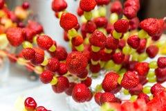 Uvas de la fresa en un palillo Dé fruto en un palillo en una tabla de banquete Imágenes de archivo libres de regalías