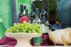 Uvas de tabela brancas na salva com vela ardente vermelha fotos de stock royalty free