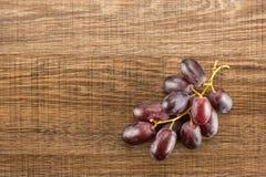 Uvas de vino rojo crudas frescas en la madera marrón Fotos de archivo libres de regalías