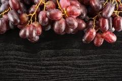 Uvas de vino rojo crudas frescas en la madera negra Fotografía de archivo