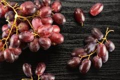 Uvas de vino rojo crudas frescas en la madera negra Imágenes de archivo libres de regalías