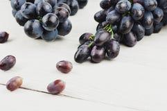 Uvas dispersadas ao lado dos grupos de uvas azuis maduras frescas em pranchas brancas de madeira velhas imagens de stock royalty free