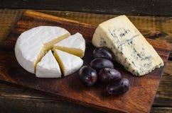 Uvas do camembert da placa de queijo na tabela de madeira Imagem de Stock