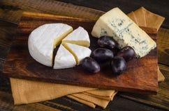 Uvas do camembert da placa de queijo na tabela de madeira Fotos de Stock