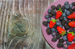 Uvas-do-monte e morangos em uma placa cor-de-rosa Fotos de Stock
