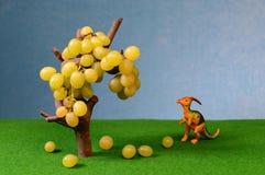 Uvas e figura frescas brancas do dinossauro Fotografia de Stock