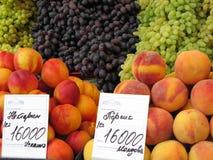 Uvas e pêssegos para a venda no mercado bielorrusso de Komarovsky dos rublos, Minsk Bielorrússia foto de stock