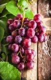 Uvas en la tabla de madera Fotografía de archivo