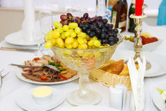 Uvas en un florero en la tabla del día de fiesta Imágenes de archivo libres de regalías