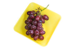 Uvas en un plato amarillo Imagen de archivo