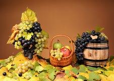 Uvas en una cesta de mimbre y manzanas Fotos de archivo