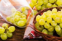 Uvas en una copa de vino y una cesta de uvas en la tabla Imágenes de archivo libres de regalías