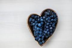 Uvas en una placa de madera de la forma del corazón Fotografía de archivo libre de regalías