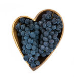Uvas en una placa de madera de la forma del corazón Imagenes de archivo