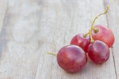 Uvas en una tabla de madera Foto de archivo