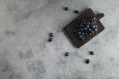 Uvas escuras na placa em um fundo cinzento textured foto de stock royalty free