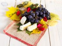 Uvas, folhas e queijo Fotografia de Stock Royalty Free