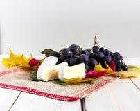 Uvas, hojas y queso Foto de archivo