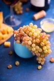 Uvas maduras deliciosas en una pequeña taza Fotos de archivo