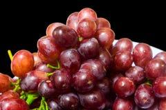 Uvas maduras en plato en fondo negro fotos de archivo