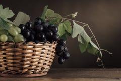 Uvas maduras en todavía de la cesta una vida Imagen de archivo