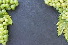 Uvas maduras en una piedra oscura foto de archivo