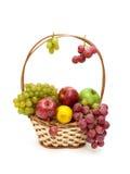 Uvas, manzanas y limón en una cesta de mimbre Imagen de archivo