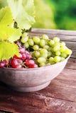 Uvas nas folhas de madeira da tabela e da uva Uvas para vinho saudáveis de fruto fresco Imagem de Stock Royalty Free