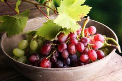 Uvas nas folhas de madeira da tabela e da uva Uvas para vinho saudáveis de fruto fresco Imagens de Stock Royalty Free