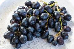 Uvas negras en la placa Fotografía de archivo